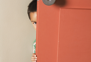 Boy hiding behind door